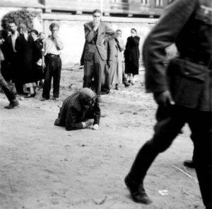Фото из коллекции Дэвида Престона показывает избитого еврея, который лежит на улице в то время, как мимо проходит немецкий солдат