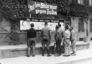Граждане Германии читают публикации Der Sturmer, Вормс, 1933. На газетном щите написано: «Со Штурмовиком против Иудеи»