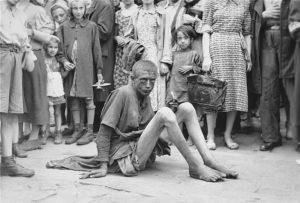 Истощенный человек, сидящий на тротуаре в Варшавском гетто
