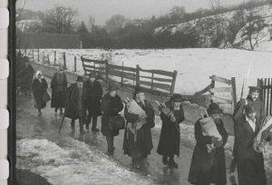 Члены еврейской общины покидают город, унося свитки Торы