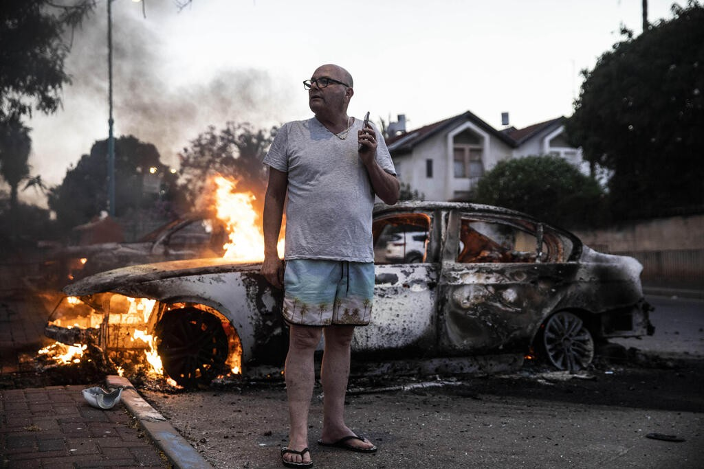 Житель Лода возле сожженной машины